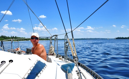 yachtsman: Zaporozhye City, Ukraine - June 13, 2010 - A yachtsman ruddering a boat during a regatta competition on the river Dnieper
