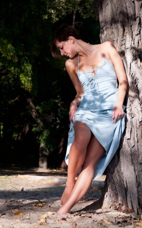 A beautiful young woman in a sun dress looking at her slender legs in the nature