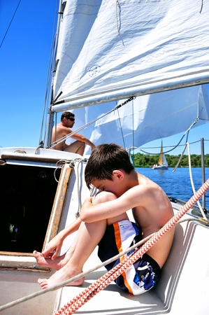 cadet blue: ZAPOROZHYE, UKRAINE, 12 JUNE 2010 � A ship�s boy sits on the bench at the deck of a yacht during a regatta on the river Dnieper