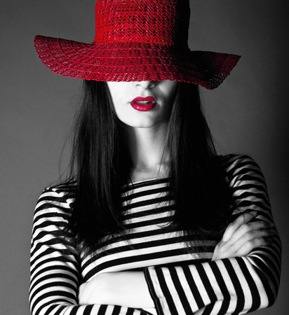 Beautiful fashion brunette woman wearing a red hat and red lipstick in studio environment