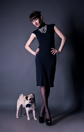 Beautiful fashion brunette girl in a dress together with a pug dog in a bow tie in a studio environment photo