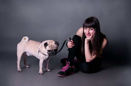 Beautiful sport brunette woman sitting on the floor and holding her pug dog on a leash in studio environment  photo