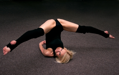 Happy pretty young sports girl smiling and doing splits on the floor Stock Photo