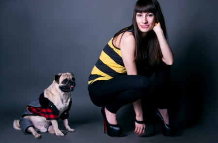 Beautiful fashion brunette girl in black leggings, stripped t-shirt and high heels with her favorite pug dog pet in funny costume against grey background Stock Photo - 14003646
