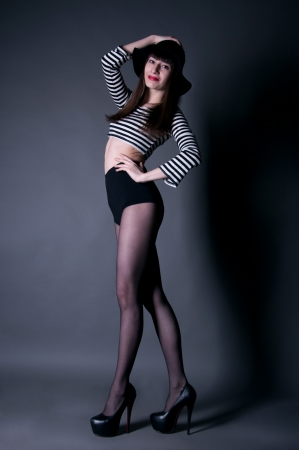 Beautiful smiling fashion brunette girl with red lips holding her black hat and crossing her long legs in tights in studio environment Stock Photo - 14003645