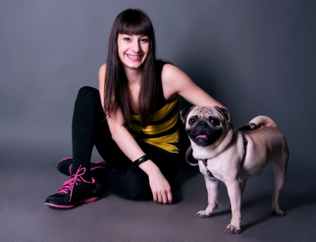 Happy beautiful sport brunette woman sitting on the floor and holding her funny pug dog pet on a leash in studio environment
