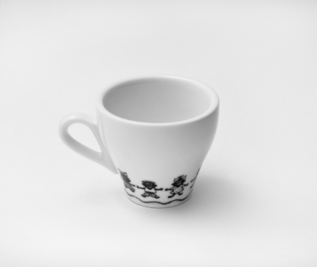 White espresso cup with black cartoon drawings of children dancing in a ring against white background photo