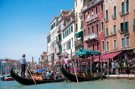 Venice, Italy - May 18, 2012 - Unknown gondoliers lead their gondolas with tourists on the board near embankment of Grand Canal