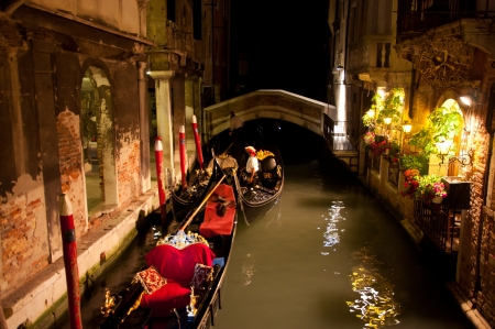 Venice, Italy - May 17, 2012 - Unknown Venetian gondoliers lay up their gondolas in one of water canals at a night time against cityscape of old buildings and illumination