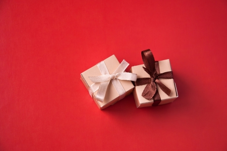 Two wrapped gift boxes with colorful satin ribbons and bows on red background in studio, Focus on a bow
