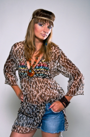 Young, bright and pretty hippie girl wearing vintage style clothes against gray background in studio  photo