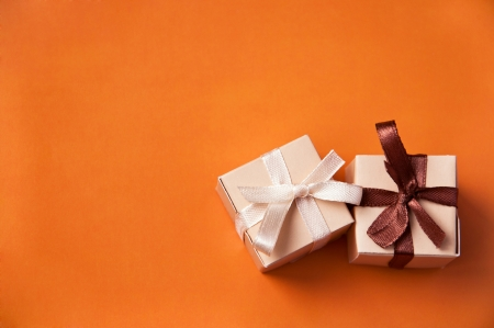 birthday gift: Two wrapped gift boxes with colorful satin ribbons and bows on orange background in studio. Focus on a bow