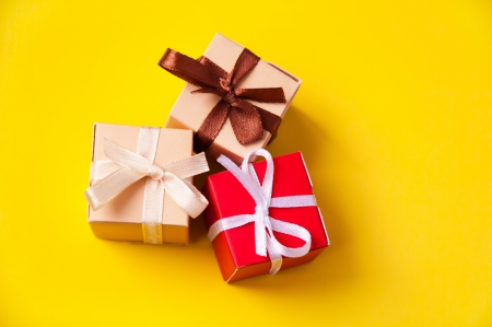Three wrapped colorful gift boxes with colorful satin ribbons and bows on yellow background in studio, Focus on a bow photo