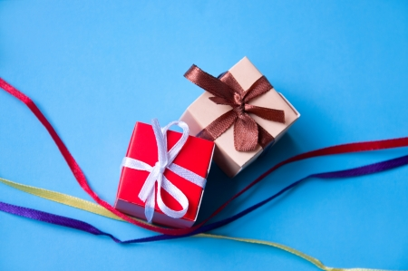 Two wrapped gift boxes with colorful satin ribbons and bows on blue background with red, yellow and violet bright ribbons crossed near them in studio. Focus on a bow photo