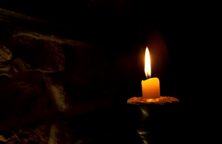 One candle in an old candlestick against brick wall background