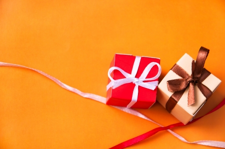 Two wrapped gift boxes with colorful satin ribbons and bows on orange background with pink and red bright ribbons crossed near them in studio. Focus on a bow Stock Photo - 14327860