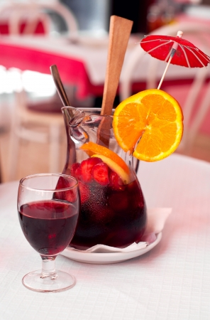 Traditional Spanish wine beverage sangria with strawberries, orange and ice on a table in cafe.  photo