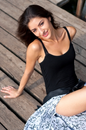 Pretty young brunette woman in black leotard and skirt sitting on wooden dock and smiling photo
