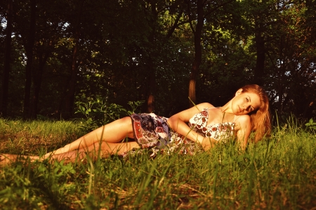 Pretty young woman in a summer dress lying on grass and looking at camera during sunset outdoors in a park photo