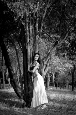 Beautiful brunette woman in black top and long white skirt standing near a cedar tree, dreaming and looking into the distance photo