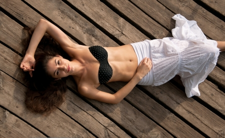 Pretty happy brunette girl in black bra with stresses and white long skirt with natural makeup lying on wooden planks outdoors Stock Photo