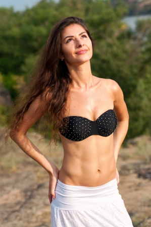 Beautiful summer athletic brunette woman with wavy hair wearing black bra and white skirt and looking up at the sky during summer day