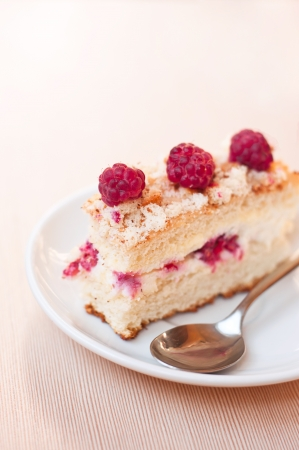 Tasty sponge cake with raspberries and curds as filling on a white plate with spoon on a textured table. Main focus on front raspberry and fore top part of the cake photo