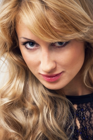 Closeup portrait of a pretty blond young girl with wavy hair, tender makeup wearing a lace top and looking at camera Stock Photo