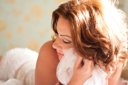 Pretty young woman with red hair wearing white lace lingerie and lying in her bed and keeping white cloth near her face. Main focus on eyes Stock Photo