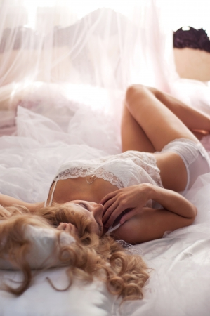 Pretty young woman in white lace lingerie (top and panties) lying on bed and enjoying her morning. Main focus on eyelashes