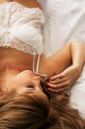 Top view on a beautiful young fashion woman with clean and tender skin wearing white lace lingerie and lying on her bed in the morning and looking at something. Main focus on the eyes  Stock Photo