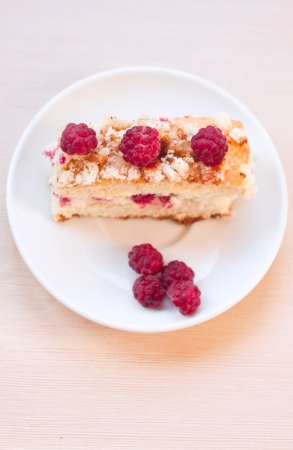 Top view on delicious sponge cake with raspberries and curds as filling with separate berries on a white plate with spoon on a textured table. Main focus on top raspberries on the cake