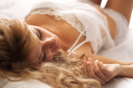Pretty young blond woman in white lace underwear sleeping on her bed early in the morning. Main focus on eyelashes