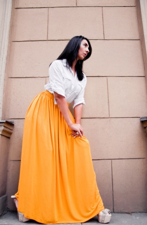 Photography from below of pretty brunette fashion female model wearing white shirt and long maxi bright yellow skirt and posing near brick wall  Stock Photo