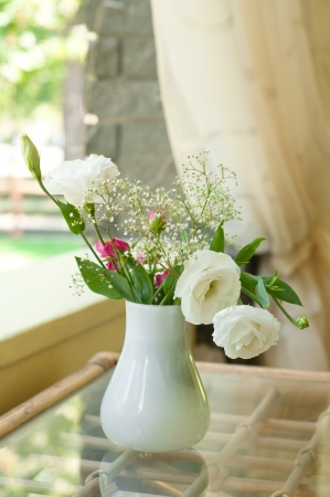 Bunch of tender fresh white and pink roses with some small flowers as decoration in a vase on a glass table in a restaurant on a bright sunny day
