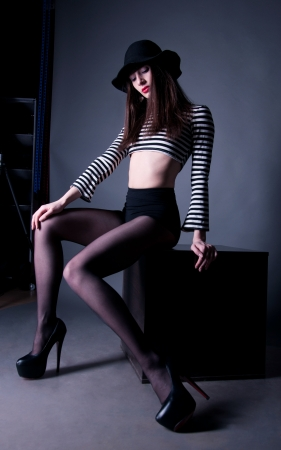 Pretty fashion brunette woman in striped top, black short, hat and stockings sitting on a cube and looking at her long slim legs on high heels against gray background in studio environment