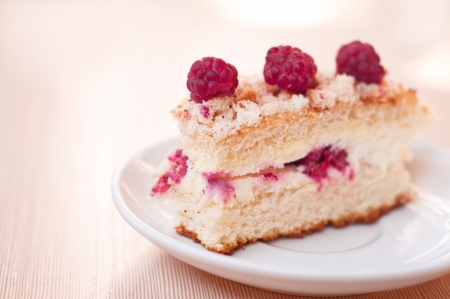 Delicious sponge cake with raspberries and curds as filling on a white plate on a textured table. Main focus on front raspberry and fore top part of the cake