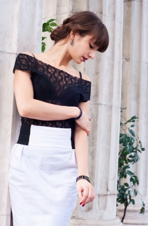 Portrait of beautiful young brunette fashion female woman wearing black lace top and white skirt and with her hair done in Greek style against old columns Stock Photo - 15408332