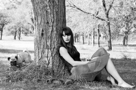 pet photography: Black and white photography of beautiful barefooted brunette woman sitting near a tree with her shoes nearby and calling her pug dog pet