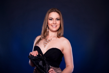 Happy toothy smiling young blonde female model in cocktail dress holding her small black purse and looking at camera against black and blue background in studio
