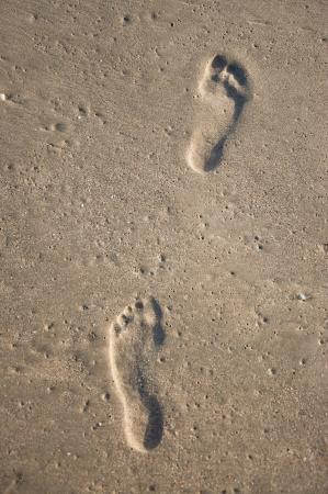 Two deep footprints of human feet on wet sand on the beach Stock Photo
