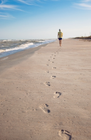 Footprints on wet sand in sunset light of one man moving ahead along coastline near the sea