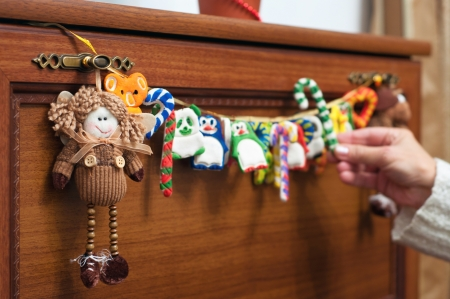 rag doll: Christmas decorations like rag doll and homemade garland with different toys & acirc,penguin, panda, candy cane and other &acirc,hanging on brown wooden chest of drawers indoors
