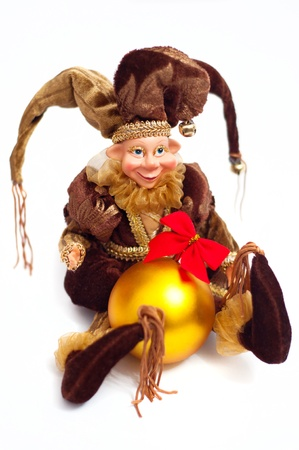 Christmas elf doll wearing beautiful brown pursuit and holding yellow sphere ball with red bow in his hands. Against white background Stock Photo - 16016546