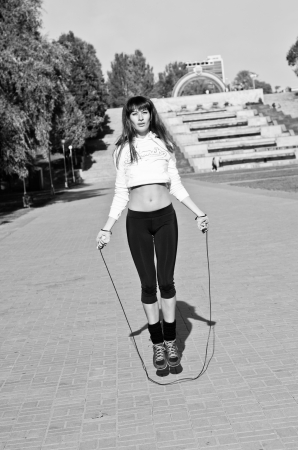 Black and white photography of young beautiful brawny sport woman jumping on a skip rope outside in the park on a bright sunny day photo