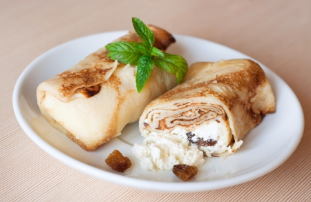 Two tasty fried pancakes stuffed with curds and raisins on white plate for breakfast on beige textured wooden table