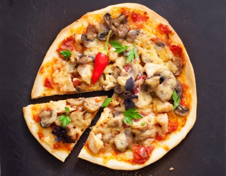 Yummy tasty pizza with cheese, mushrooms, basil, chicken, tomato sauce, chilli pepper and parsley with one portion piece cut against dark brown table background with dough crumbs photo