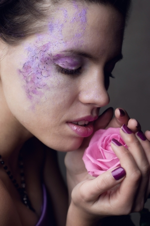 Beautiful young brunette woman closing her eyes in pleasure and wearing extraordinary purple and pink makeup, light pink lipstick, having her nails covered with purple enamel, holding tender pink rose in her hands and smelling it photo