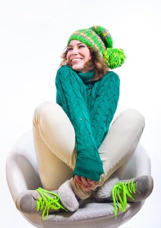 ropa de invierno: Linda chica divertida con ropa de invierno como suéter de punto verde y un sombrero de color amarillo brillante con pom-pon, sentado en una silla blanca, sonriendo y riendo con los ojos cerrados, las manos y las piernas cruzadas. Aislado sobre fondo blanco. Copiar el espacio