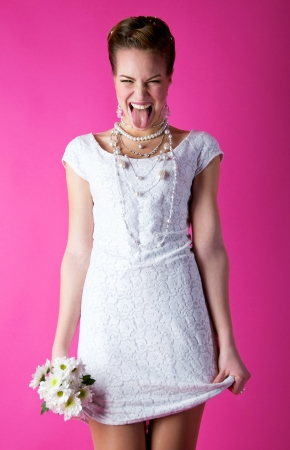 Portrait of naughty young funny girl bride holding her dress and bunch of flowers and making funny face on pink background  Stock Photo - 16935249